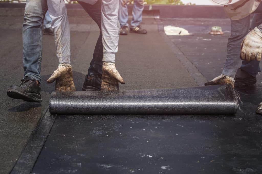 Grand Building and Remodeling professional installs underlayment on a residental roof.